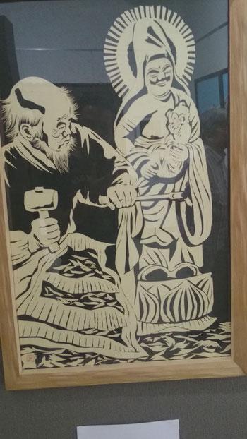 子抱菩薩像を掘る木喰の切り絵(画のようですが、黒い台紙に切り絵を張り付けただけの手法です)