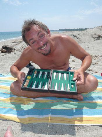 Skipper Jochen spielt Backgammon am Strand