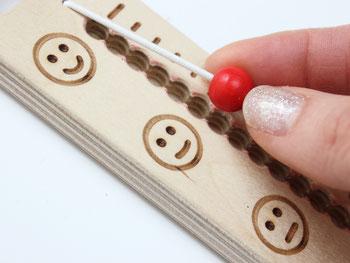Auch eine Erzieherin hält ein Gefühlebarometer oder Gefühleregler in der Hand. Zu Beginn des Morgenkreises in der Kita kann auch sie die Perle verschieben und erzählen, wie sie sich heute fühlt.