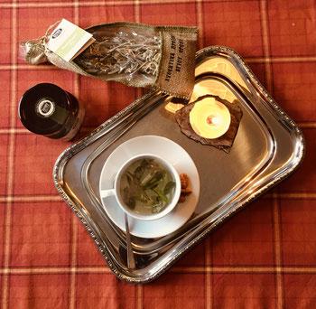 Griechischer Bergtee in der Tasse auf einem Tablett mit Kerze und Griechischem Pinienhonig