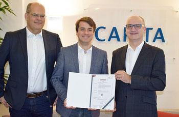 Dr. Peter Jonas (rechts) übergibt am Berliner Capita Standort die Zertifizierungsurkunde an Bernd Moll (links) und Sebastian Seyrl (Mitte).