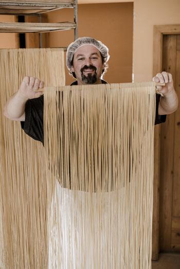 Joffrey Melchart hält zum Trocknen aufgehängte Spaghetti
