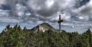 Gipfelkreuz des Breitenstein mit Geigelstein im Hintergrund
