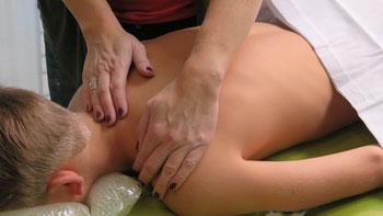 Hier führt die Praxisleitung eine klassische Massage am Rücken eines Patienten durch. Die Massage kann sich über den gesamten Körper erstrecken. Auch hier wird die Behandlung auf der Massageliege vorgenommen.