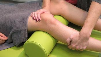 Auf dem Foto behandelt Frau Tollas das verletzte Knie eines auf einer Behandlungsliege liegenden Patienten in der klassischen Form einer physiotherapeutischen Behandlung.