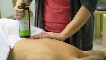 In dieser Aromamassage behandelt Frau Tollas einen Patienten welcher auf einer Liege auf dem Bauch liegt. Zur weiteren Darstellung dieser vielfältigen Behandlungsmöglichkeiten hält Frau Tollas eine Flasche mit einem beispielhaften Duftaroma in der Hand.