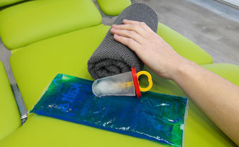 Auf einer Liege befinden sich kälteführende Matarielien die für die Kryotherapie benötigt werden. Hier wird gerade eine Hand, welche auf einem Handtuch liegt in der Kryotherapie behandelt.