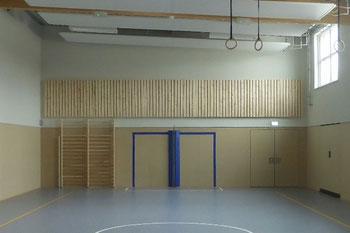 nachgebesserte Stirnwand derselben Sporthalle mit Absorberfries über der Prallwand