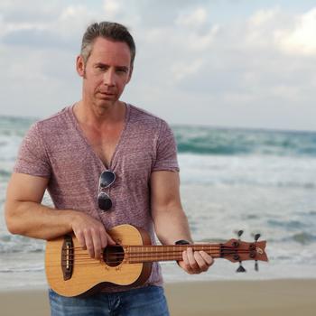 Detlev Gebers mit Bass Ukulele Ortega Lizzy Bassist am Strand