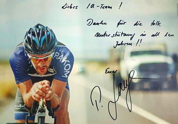 Triathlonprofi und Ironman-Weltmeister Patrick Lange auf der Radstrecke mit Danksagung an iQ athletik