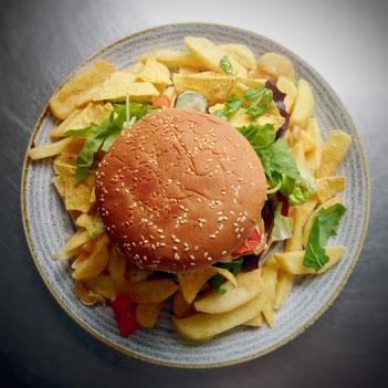 Burger in der Mitte von Pommes auf Teller von oben