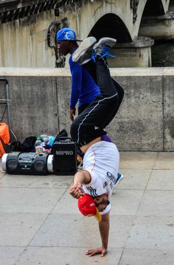 Volksfeststimmung herrscht immer unterhalb des Eiffelturms. Da versuchen sich Breakdancer genauso wie Zauberer und andere Artisten, um die Aufmerksamkeit der Touristen auf sich zu ziehen und so ganz nebenbei noch ein bisschen Geld in die Kasse zu spülen.