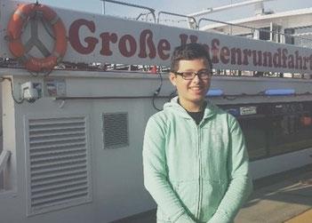 SOMMERUNTERNEHMER Stani am Hamburger Hafen vor einer Barkasse von Barkassen Meyer
