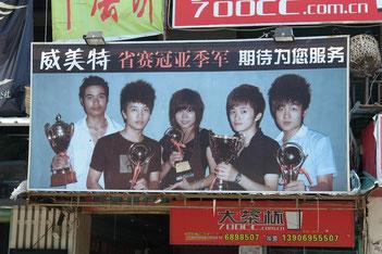 Reklametafel eines Friseursalons in einem ländlichen Gebiet. Während vor einigen Jahren diese toupierten Frisuren als cool galten, sieht man sie heute nur noch in ländlichen Gebieten, oder unter junge