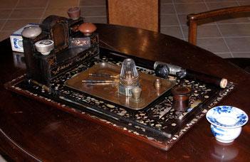 Plateau portant un nécessaire de fumeur d'opium complet : pipe, lampe, fourneaux, outils et ringard.