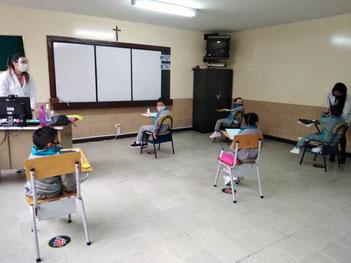Eine Lehrerin und eine Hilfskraft ermöglichen den Schulunterricht in Belen.