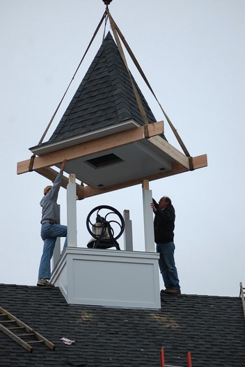 Neil Ruffner, right, and Rick DeVree of Ruffner Construction Inc., work to place the bell tower roof on its base on the roof of New Groningen School, which is being renovated by the Zeeland Historic Society.
