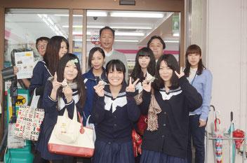 発売されるおにぎりを手にする(前列右から)比嘉さん、新城さん、木村さん。後列は、高校生を応援する長嶺勉店長(左端)ら=ココストア石垣市役所前店、23日