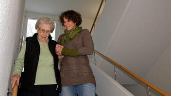 Eine Senioren-Assistentin begleitet eine ältere Frau.