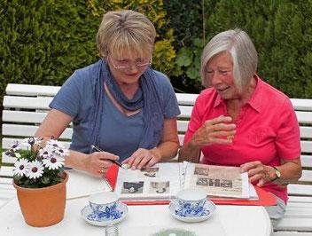 Senioren-Assistentin sieht sich mit Senioren ein Fotoalbum an.