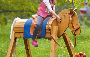 Ein Holzpferd, auf dem ein kleines Kind innerhalb der Gartenanlage sitzt.