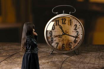 Petite fille brune qui regarde un réveil géant. La petite fille porte une jupe noire et un blaser noir. Le réveil est vieux et rouillé.