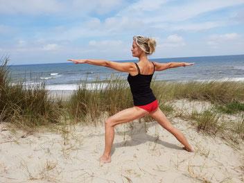 Mieke beoefent yoga op het strand