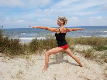 Mieke Nakken beoefent yoga op het strand tijdens het yoga wandelweekend