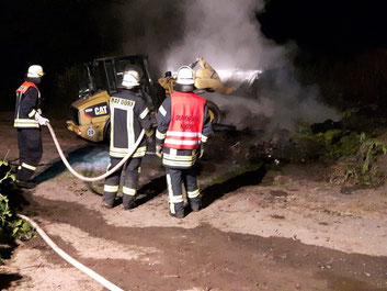Drei Feuerwehrleute mit Schlauch und Radlader, der rauchenden Stroh verteilt