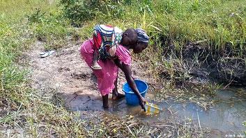 Una giovane madre nigeriana raccoglie acqua infetta per destinarla agli usi domestici