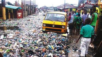 Le drammatiche condizioni igieniche di una strada sommersa dai rifiuti in Nigeria