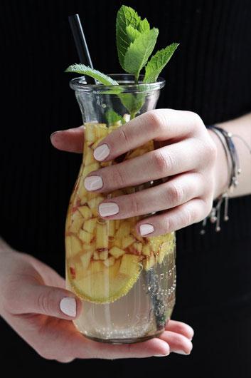 eine Person hält ein Glas Nektarinenbowle