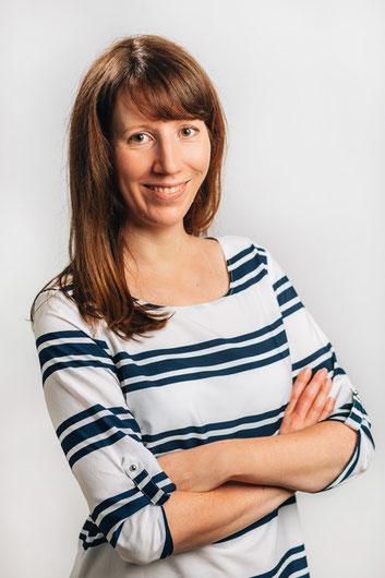 Portrait Jana Scheidemann: Bildausschnitt von Kopf bis Bauch, die Arme sind locker vor dem Bauch verschränkt, sie lächelt direkt in die Kamera, rotbraune glatte Haare - mittellang, braune Augen, trägt eine weiße Bluse mit dunkelblauen Streifen.