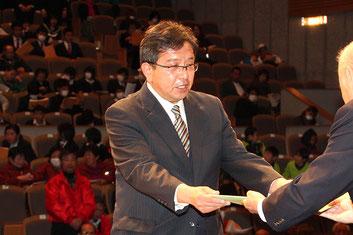 優秀指導者賞と指導者奨励賞を代表し、梅堀智氏が壇上へ