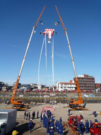 1月に行われる出初式の風景。やぐらに見立てた昭和クレーンの共吊り。(当社のクレーンで吊るした薪から煙があがり、そこにめがけて多くの消防車が一斉に放水をします)