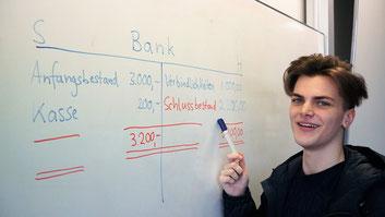 Im Berufskolleg Wirtschaftsinformatik lernt ein Schüler Buchhaltung und Rechnungswesen im BWL-Unterricht (Betriebswirtschaftslehre)