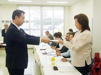川満町長から竹富町景観計画審議会委員へ委嘱状が手渡された=10日午後、離島ターミナル