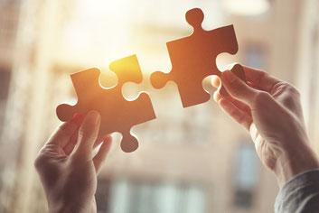 Hände halten zwei Puzzle-Teile in die Sonne: Journalismus setzt einzelne Puzzle-Stücke von Informationen zu einem Gesamtbild zusammen
