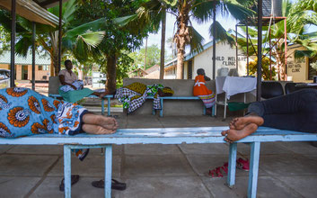 """Im Wartebereich der """"Child Welfare"""" Klinik liegen Patienten auf den Bänken und warten auf den Arzt."""