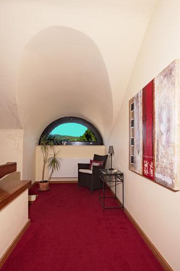 Immobilienfoto: Blick durch ein halbrundes Fenster, innen geblitzt mit heller Außensicht