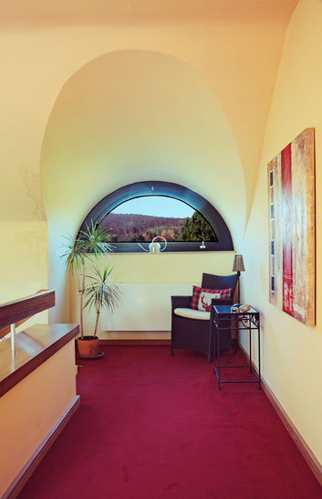Immobilienfoto: Blick durch ein halbrundes Fenster, sowohl Landschaft draußen als auch der Innenraum korrekt belichtet