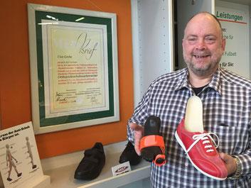Orthopädie-Schuhmachermeister Uwe Grebe vor seiner Meisterbrief-Urkunde im City-Service Bottrop. Orthopädisches Hilfsmittel plus Joya Technologie