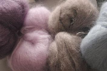 4 Wollknäuel in Pastellfarben lila, hellrosa, hellgraubraun und hellblau nebeneinander
