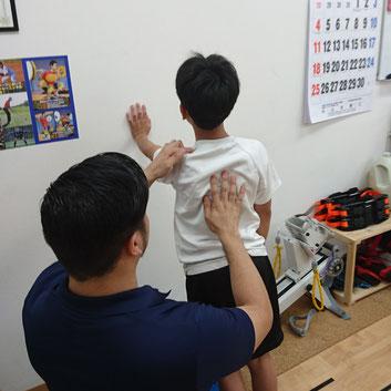 肩首の力を抜いて、肩甲骨で操作して安定した押し手ができるよう「壁」を押して練習・指導中の写真