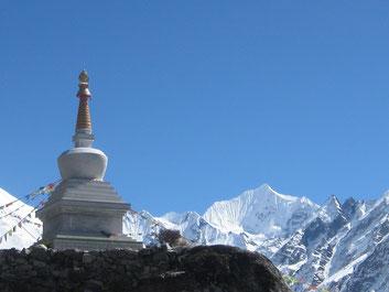 Buddhistischer STupa mit Bergen dahinter und viel Himmel. Foto: Karma Lama