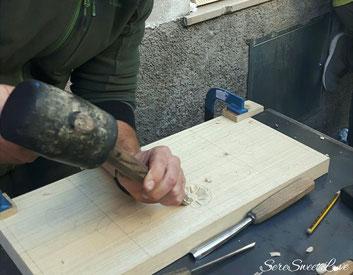 Lavorazione a mano con scalpello dal giovane artigiano per la creazione del tagliere.