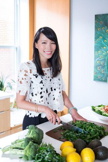 Portrait photo coach professionnelle nutritionniste femme Julie Doan dans sa cuisine en train de couper du persil à Montréal dans le quartier Villeray par Marie Deschene photographe Pakolla