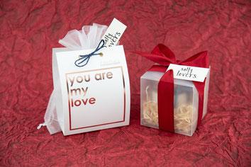 Geschenkverpackung Valentinstag vor rotem Hintergrund