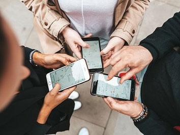 Drei Menschen stehen im Kreis und blicken auf ihre Handys, mit denen sie online eine günstige ERGO Gruppen-Reiserücktritts-Versicherung gebucht haben