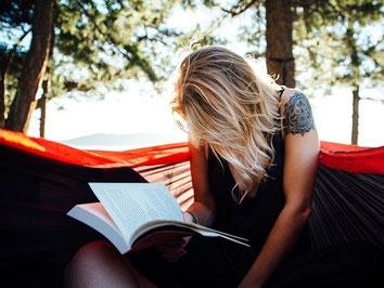 Outdoor-Seminar - Frau mit blonden Haaren sitzt in der Hängematte und lernt aus einem Buch, gut abgesichert mit einer Seminar-Versicherung der ERGO